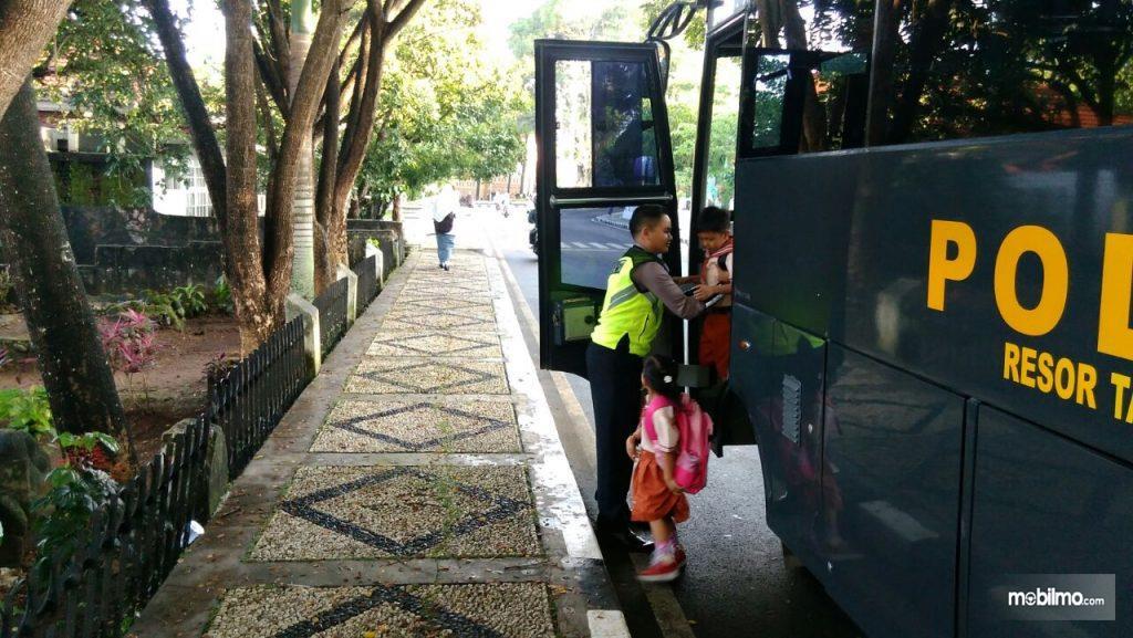 Foto seorang anak turun dari bus sekolah dibantu petugas