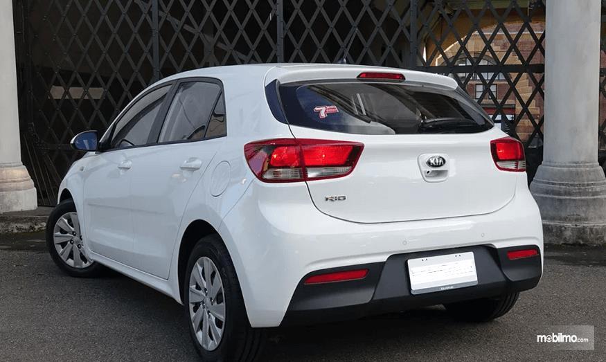 Gambar ini menunjukkan mobil KIA warna putih tampak bagian belakang