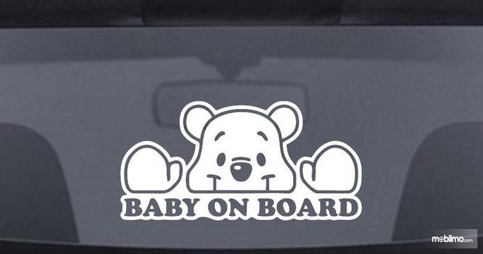 Gambar ini menunjukkan stiker baby on board pada kaca belakang