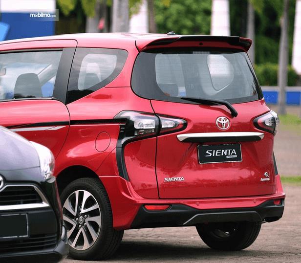 Gambar ini menunjukkan bagian belakang Toyota Sienta warna merah dan terdapat mobil lain warna hitam
