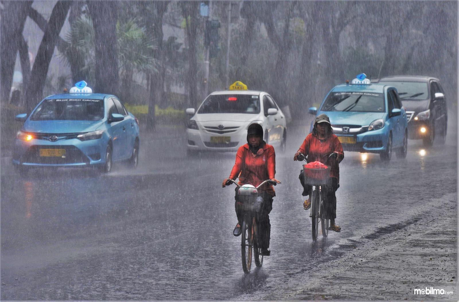 Dua orang mengayuh sepeda di tengah hujan lebat