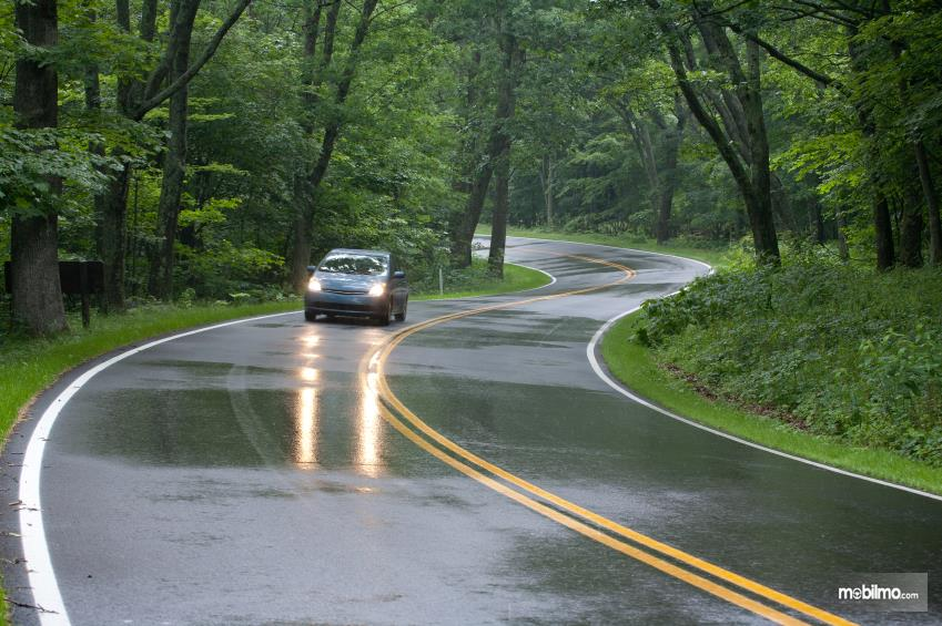 Foto jalan raya tampak licin karena basah