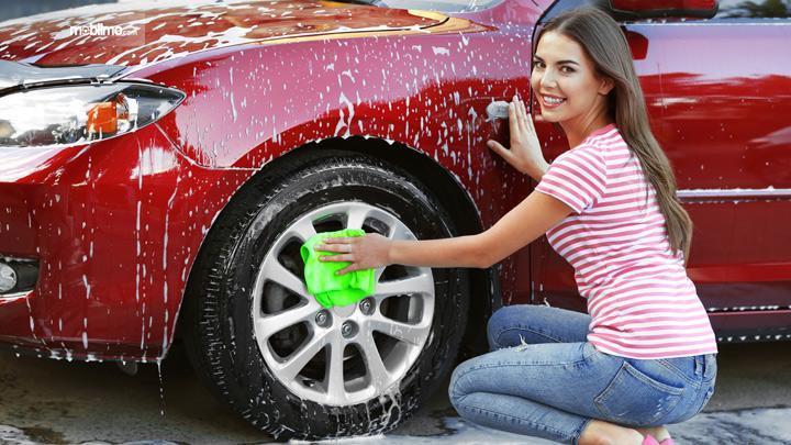 Foto seorang gadis sedang mencuci mobil