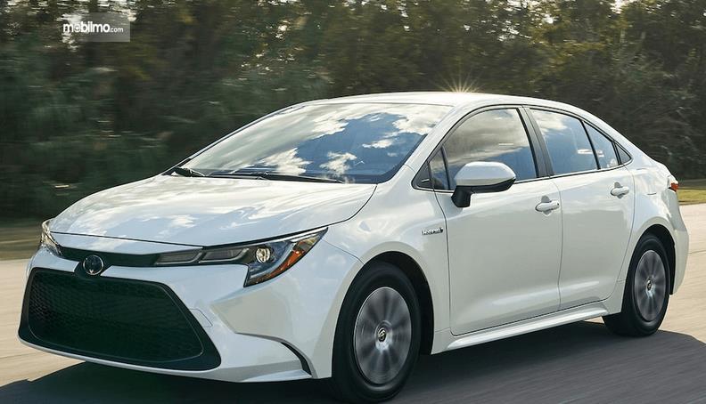 Gambar ini menunjukkan mobil Toyota Corolla Bermesin Mesin Hybrid warna putih tampak samping