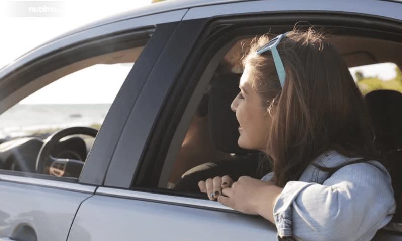Gambar ini menunjukkan seorang wanita sedang duduk di kursi belakang dengan melihat keadaan sekitar