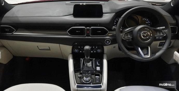 Gambar ini menunjukkan interior depan Mazda CX-8 tampak dashboard, kemudi dan head unit