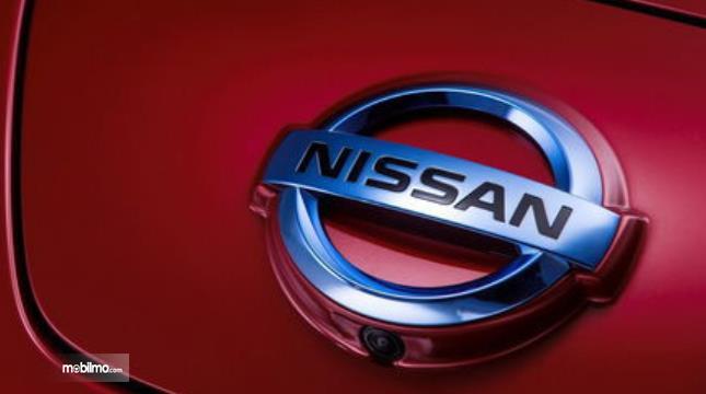 Gambar ini menunjukkan logo nissan warna krom pada mobil warna merah