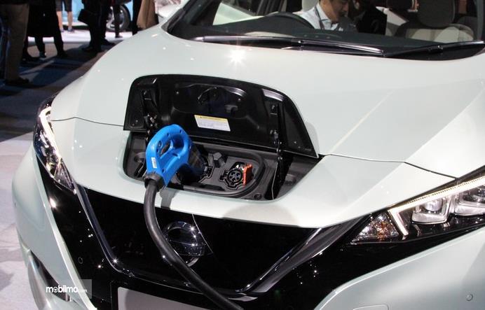 Gambar ini menunjukkan proses pengisian daya listrik pada mobil Nissan Leaf warna putih