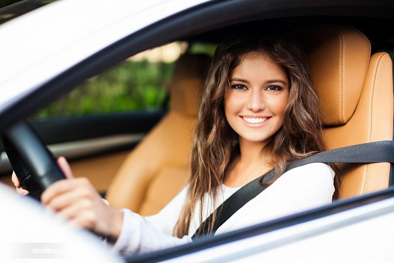 Foto pengemudi wanita sedang tersenyum