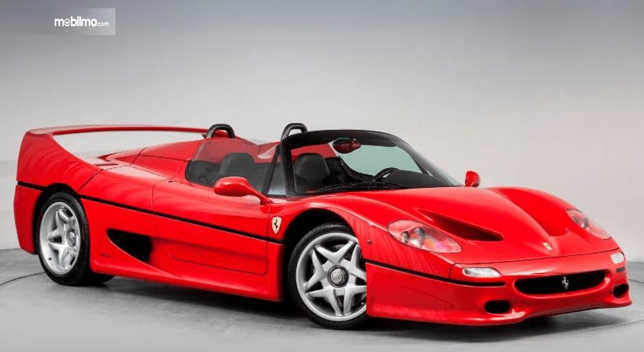 Gambar ini menunjukkan mobil ferrari merah tanpak samping kanan dan depan