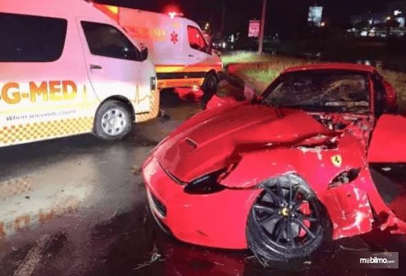 Gambar ini menunjukkan sebuah mobil merah ringsek karena kecelakaan