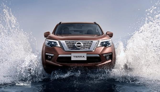 Gambar ini menunjukkan mobil Nissan Terra sedang melaju di jalanan yang terdapat air