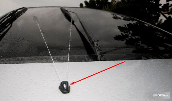 Gambar ini menunjukkan air wisher disemprotkan pada kaca mobil
