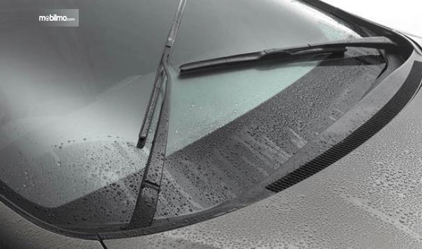 Gambar ini menunjukkan kaca mobil dan wiper dalam kondisi basah