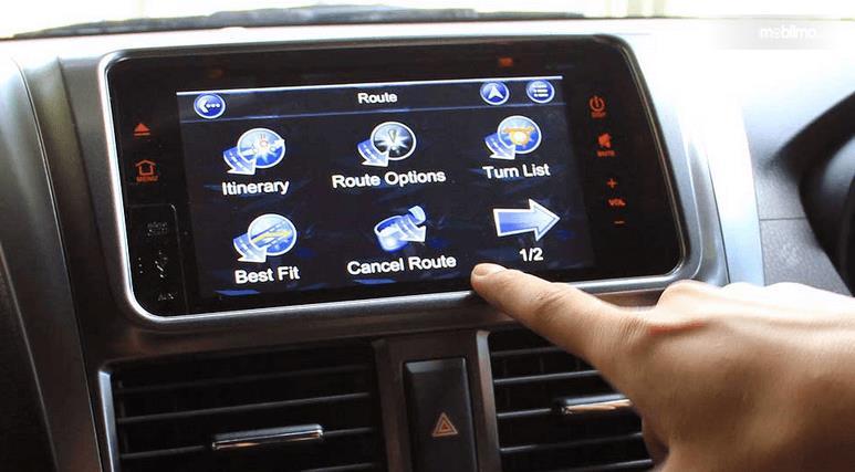 Gambar ini menunjukkan sebuah jari menunjuk pada layar head unit pada mobil