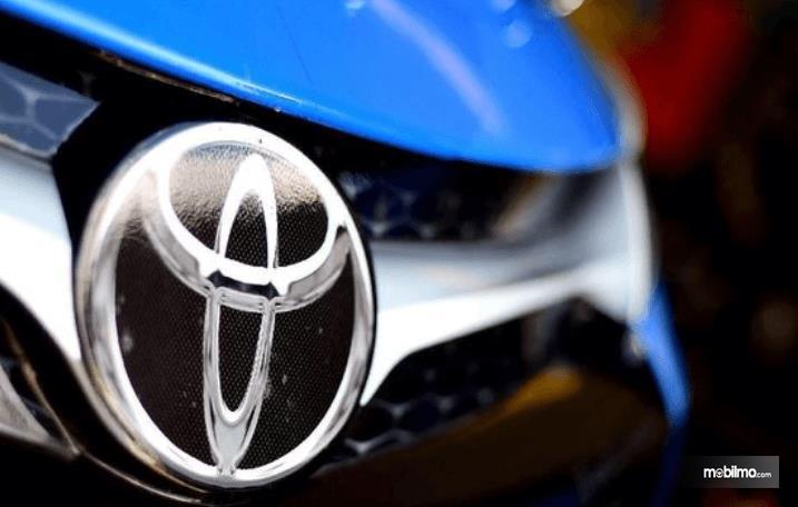 Gambar ini menunjukkan logo Toyota pada mobil warna biru