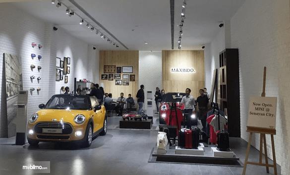 Gambar ini menunjukkan Mini Maxindo pop-up store yang terdapat 2 mobil mini warna kuning dan merah