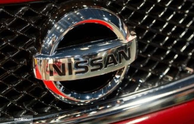 Gambar ini menunjukkan logo Nissan Leaf warna krom
