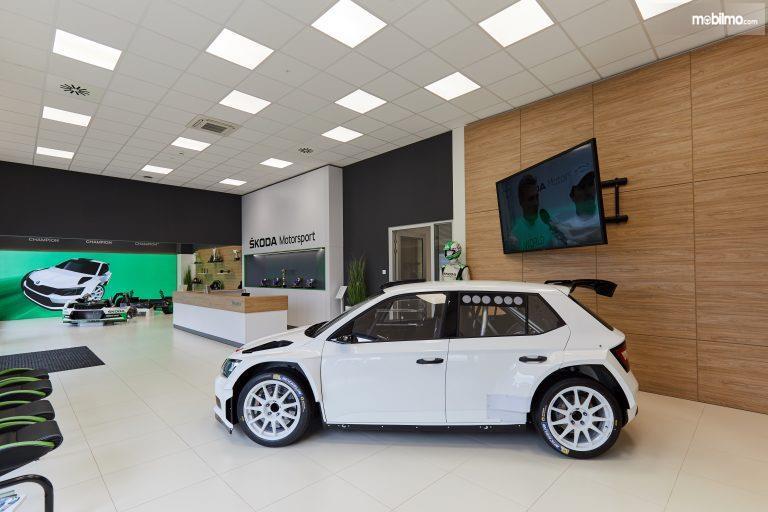 Tampak Isi diler Skoda Motosport dengan gambar sebuah mobil berwarna putih dilihat dari sisi samping