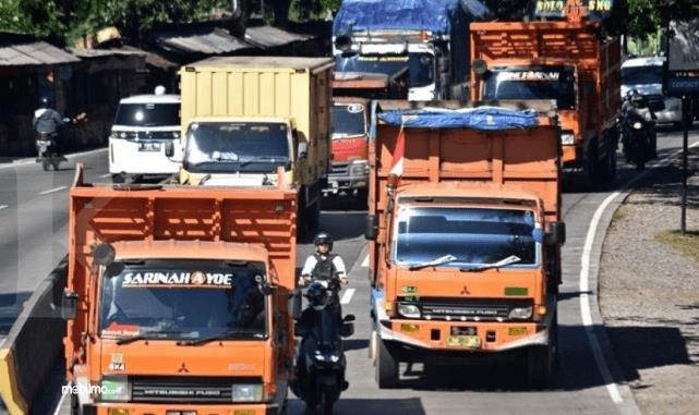 Gambar ini menunjukkan beberapa mobil truk dan kendaraan sedang melaju di jalan
