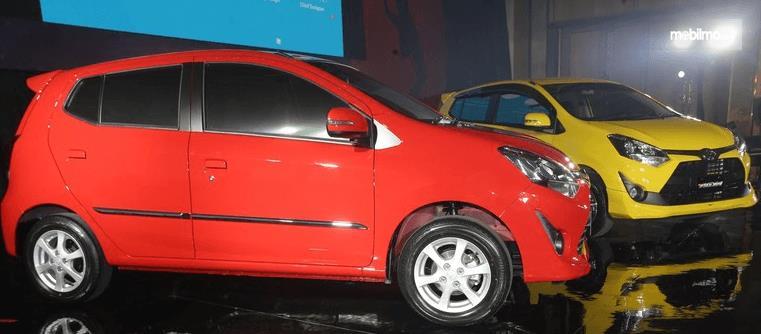 Gambar ini menunjukkan 2 buah mobil LCGC warna merah dan kuning