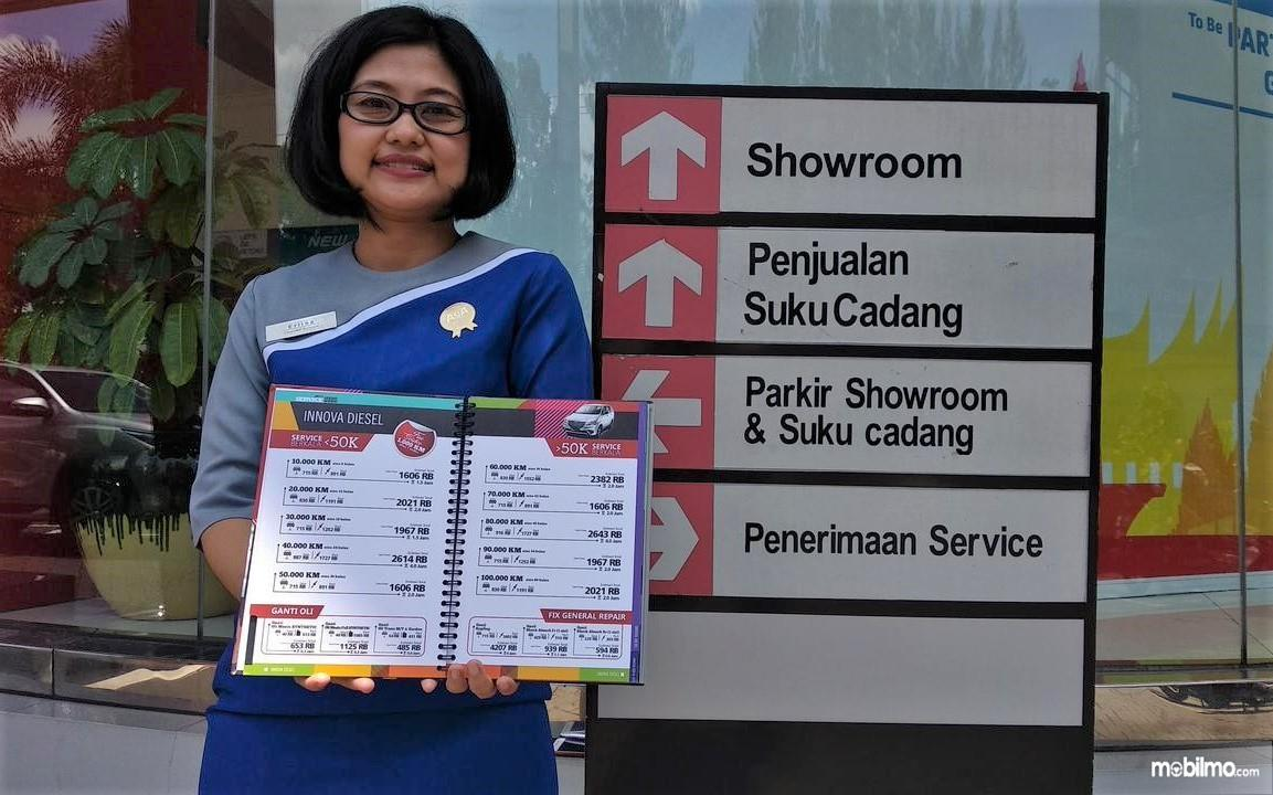 Seorang pegawai di Diler Auto2000 Surabaya menunjukkan buku katalog biaya servis