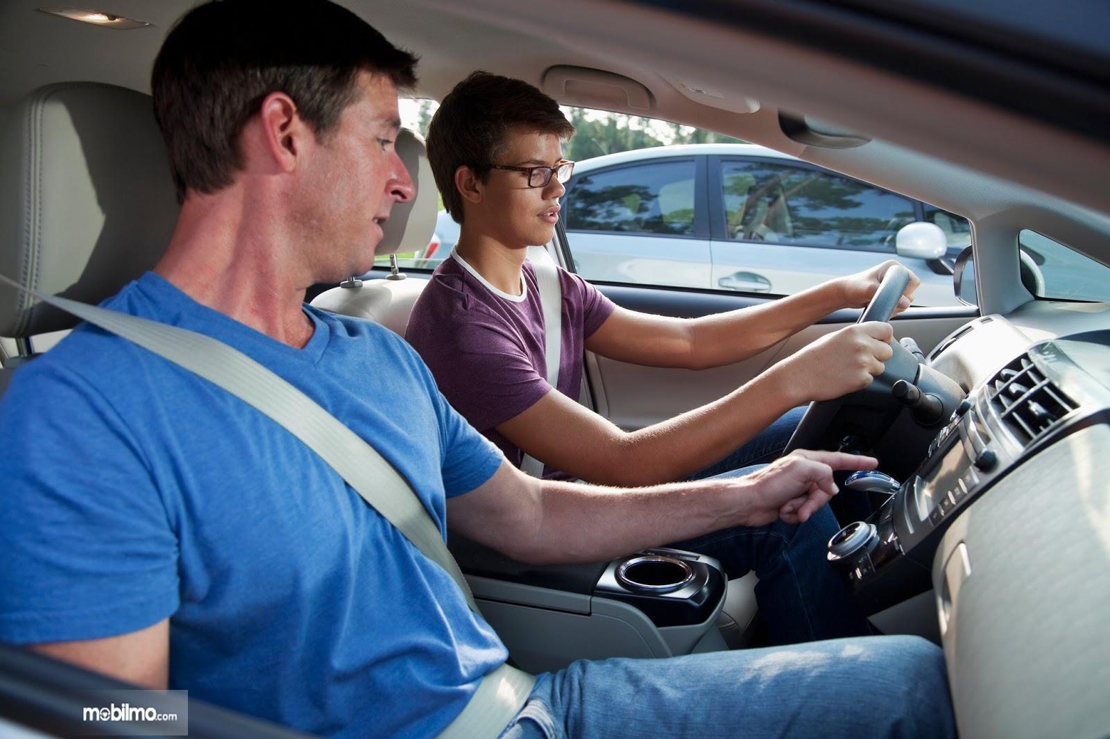 Seorang pelatih sedang memberikan arahan kepada siswa mengemudi