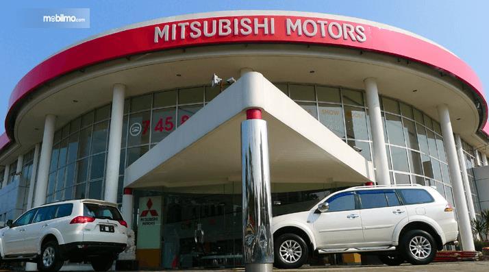 Gambar ini menunjukkan salah satu diler Mitsubishi Motors dan di depannya ada 2 mobil
