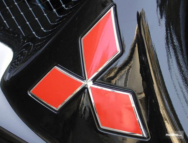 Gambar ini menunjukkan logo Mitsubishi warna merah pada mobil