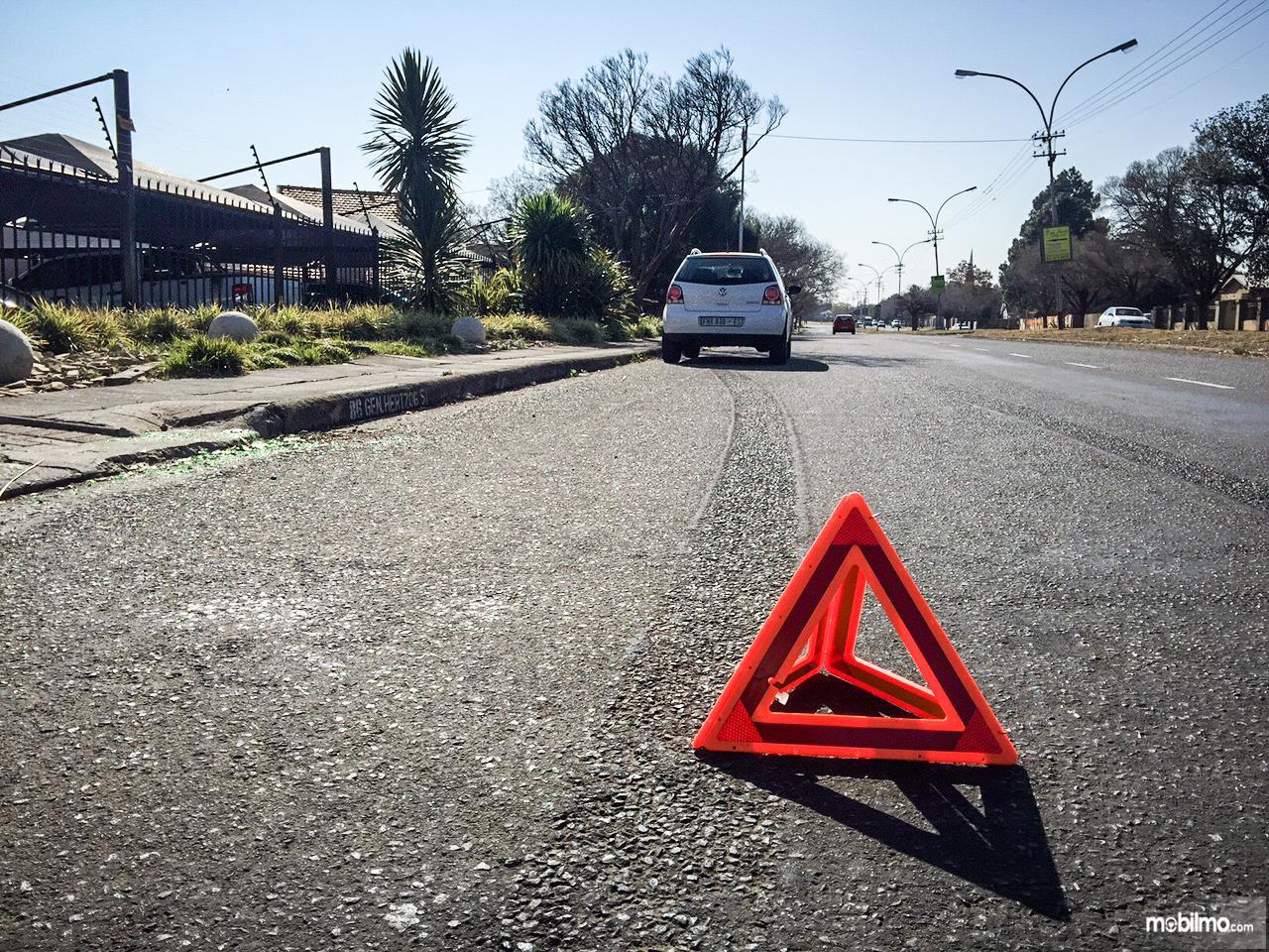 Pasang segitiga darurat agar proses pertolongan tetap aman