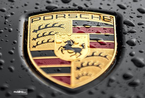 Gambar ini menunjukkan logo Porsche dalam keadaan basah