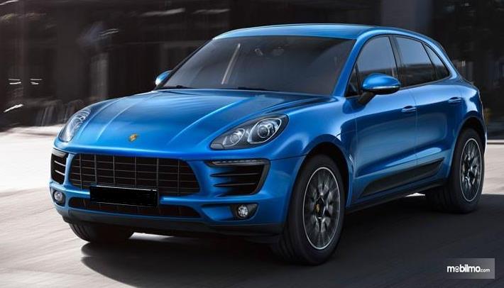 Gambar ini menunjukkan mobil Porsche Macan warna biru tampak bagin depan