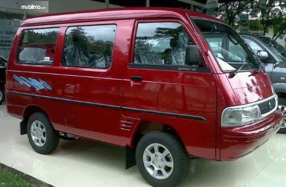 Gambar ini menunjukkan mobil Suzuki Carry Real Van 2015 warna merah tampak samping