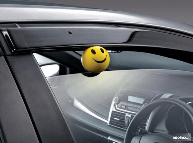 Gambar ini menunjukkan bola warna kuning terjepit jendela mobil