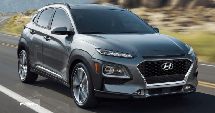 Gambar ini menunjukkan mobil Hyundai Kona warna silver gelap melaju di jalanan