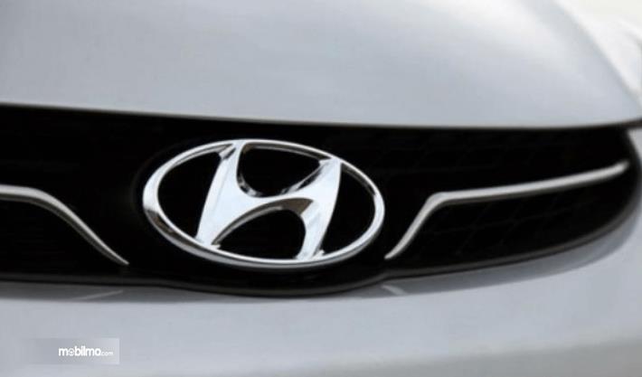 Gambar ini menunjukkan logo mobil Hyundai pada mobil warna putih