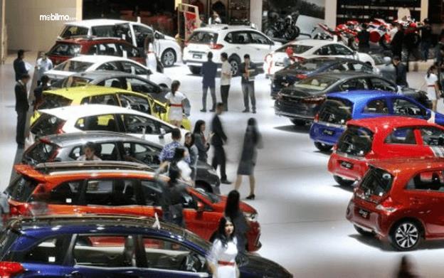 Gambar ini menunjukkan beberapa mobil sedang berada di sebuah pameran