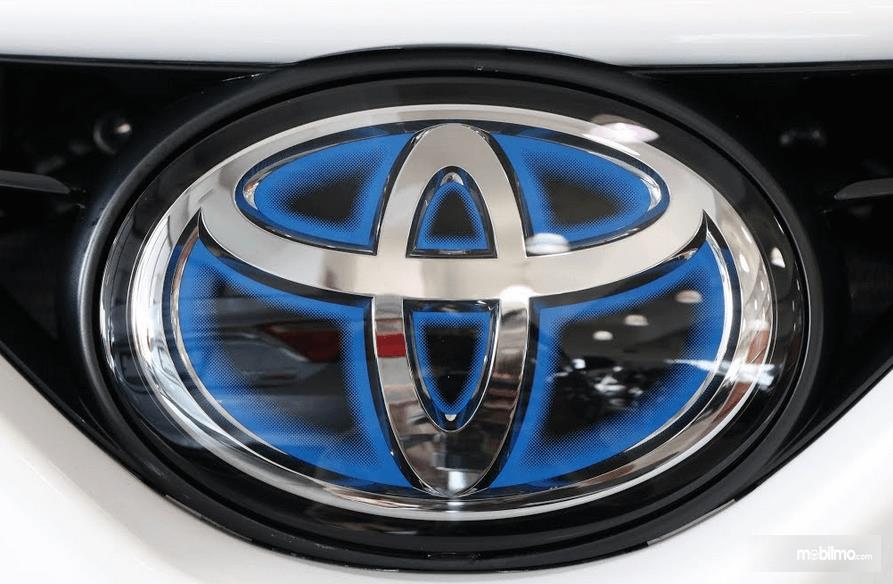 Gambar ini menunjukkan logo mobil Toyota dengan aksen warna krom dan biru