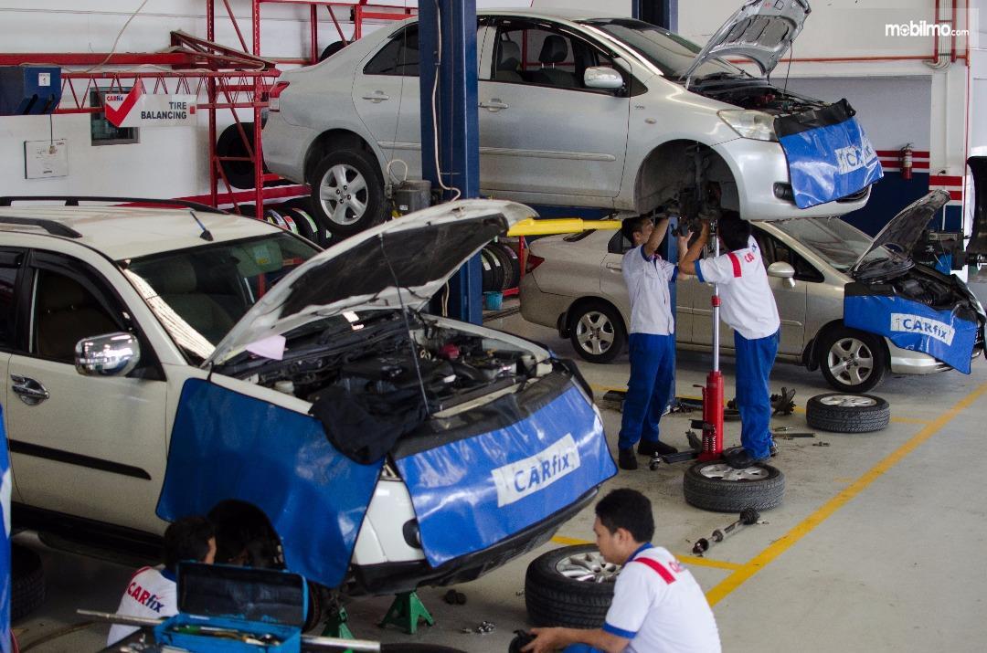 Foto para mekanik Carfix sedang melakukan proses perawatan mobil