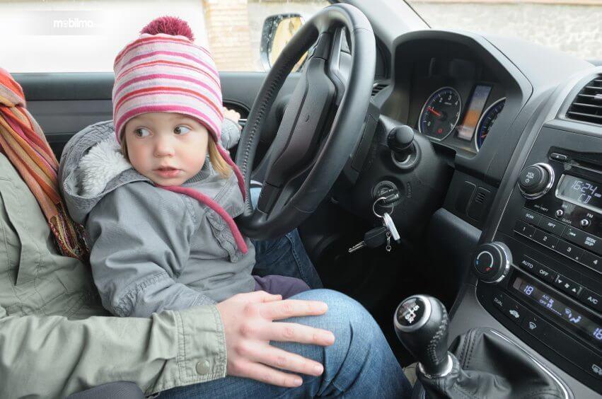 Gambaran mengemudi sambil memangku anak, sangat tidak dianjurkan karena potensi bahaya yang sangat besar