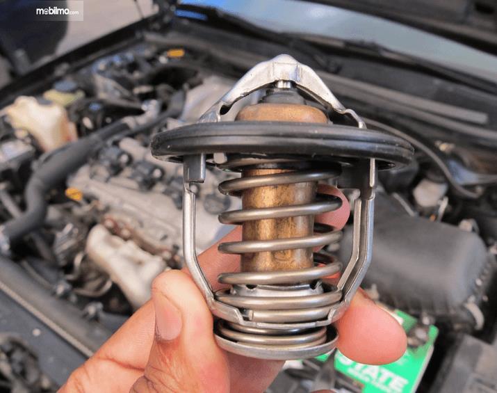 Gambar ini menunjukkan Thermostat pada mesin mobil