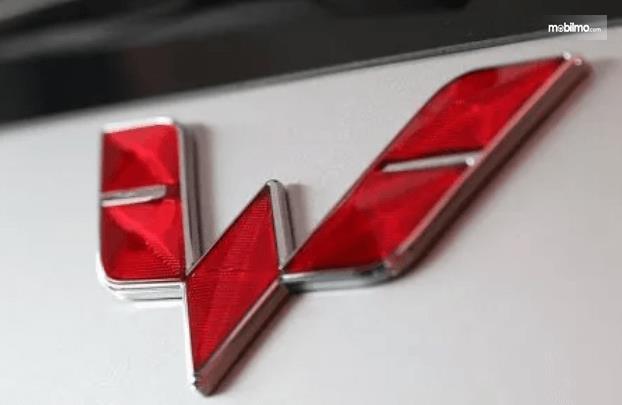 Gambar ini menunjukkan logo Wuling warna merah pada mobil warna putih
