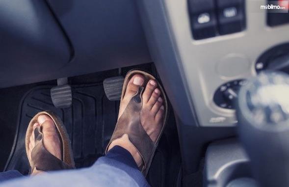 Gambar ini menunjukkan 2 buah kaki di dekat pedal pada mobil