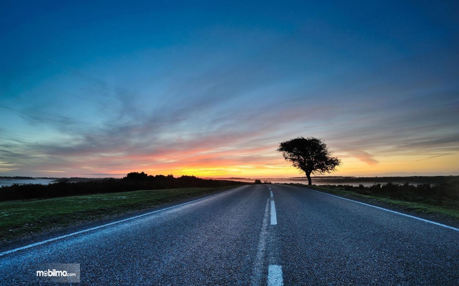 Foto jalan raya di senja hari dalam kondisi sangat lengang