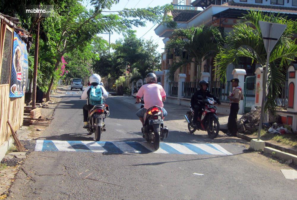 Beberapa sepeda motor tampak melintasi polisi tidur yang dibuat di jalanan pemukiman