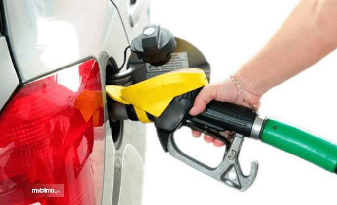 Gambar ini menunjukkan sebuah tangan memegang alat pengisi bahan bakar