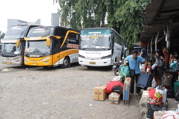 Gambar ini menunjukkan beberapa orang membawa barang bawaan banyak di terminal Bus