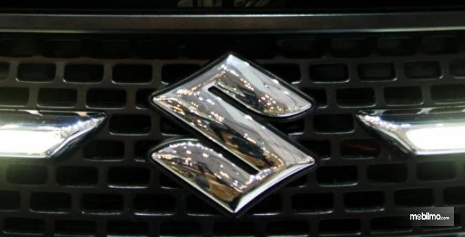 Gambar ini menunjukkan logo Suzuki pada kendaraan dengan warna krom