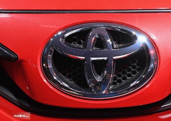 Gambar ini menunjukkan logo Toyota pada mobil warna merah