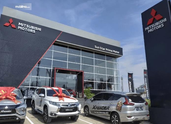 Gambar ini menunjukkan 3 mobil berada di depan diler Mitsubishi